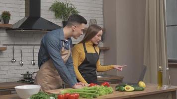 pareja mira la receta en la computadora portátil en la cocina para ensalada orgánica. marido y mujer cocinando comida receta. feliz estilo de vida saludable juntos. familia en busca de comida en línea. foto