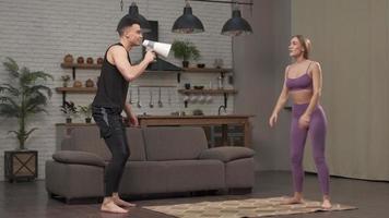 bajo ángulo de entrenador personal gritando a la mujer joven mientras hace sentadillas con la cuerda durante el entrenamiento intensivo de entrenamiento cruzado. haciendo deporte en casa foto