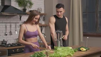 muscular young couple cooking healthy cocktail after workout, talking and laughing in the kitchen. Sport, diet, healthy food concept, slow motion photo