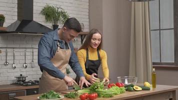 feliz pareja disfrutando de cocinar juntos en casa. Vista lateral del joven cortando verduras para la cena y hablando con su novia de pie cerca. alegre, hombre y mujer, enamorado, hacer, cena foto