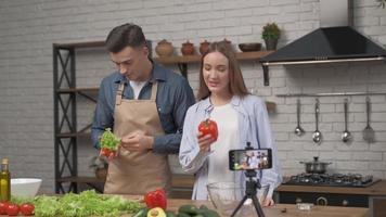 Young attractive couple bloggers shooting video food blog on mobile phone about cooking in the kitchen photo