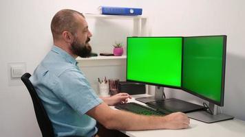 oficial masculino trabaja en una computadora con dos maquetas de pantalla verde en casa. los empleados se sientan frente a las pantallas. foto