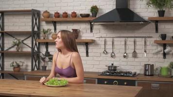 mujer sentada a la mesa, triste y aburrida con la dieta sin querer comer ensalada. interior de cocina moderna. un hombre gritando por un megáfono a una mujer foto