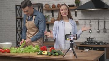 online blogging, mobile phone makes video for subscribers how bloggers couple cook preparing healthy meals from fresh vegetables and greens close up on kitchen table photo