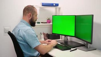 Hombre barbudo bebiendo agua de un vaso sentado en una mesa frente a dos pantallas clave de croma verde de cerca 4k. foto