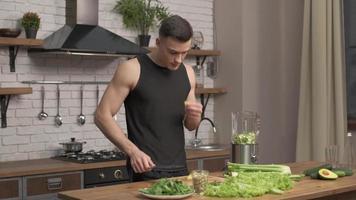 hombre atleta preparando ingredientes para batido en una cocina moderna. preparación de verduras para desintoxicación en licuadora. aguacate, apio, pepino en licuadora olla plateada en segundo plano. full HD foto