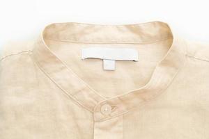 Camisa beige doblada aislado sobre fondo blanco. foto