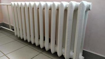 Indoor heating radiator. Cast iron radiators heat the room. photo