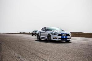 City, Country, MMM DD, YYYY - Ford Mustang on a race track photo