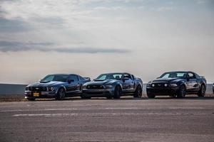 City, Country, MMM DD, YYYY - Ford Mustangs on a race track photo