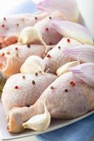 Raw chicken legs with vegetables for cooking photo