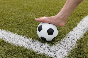 Girl's foot on the soccer ball on green field morning photo