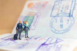 Pareja de personas en miniatura de pie en el pasaporte con sello de inmigración foto