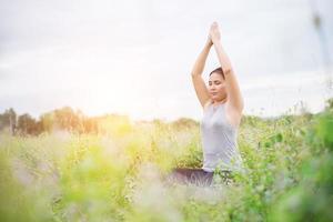 hermosa mujer de yoga practicando yoga en los prados. foto