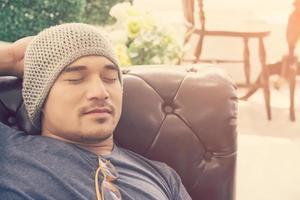 Hombre guapo joven inconformista durmiendo en el sofá en casa, foto