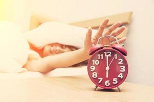 Young woman frowning in bed and holding hand on red alarm clock. photo