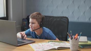 retrato de un niño enseñando lecciones en línea a distancia usando una computadora portátil e internet a través de un chat de video. aprendizaje a distancia en casa. foto