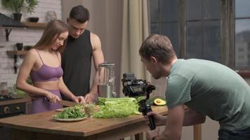 videographer filming kitchen scene. couple in love preparing healthy meal at home kitchen photo
