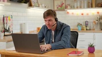 jugador masculino usando audífonos, jugando un videojuego en su computadora portátil en la cocina de casa. hombre alegre está jugando en un juego emocional. jugando juegos en cuarentena. estilo de vida de los jugadores. foto
