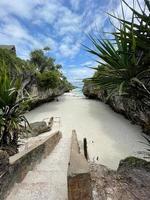 escaleras entre rocas que se dirigen a una playa. zanzíbar. viajar a un país exótico foto