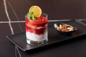 Layered dessert with fruits, nuts and cream cheese in glass photo
