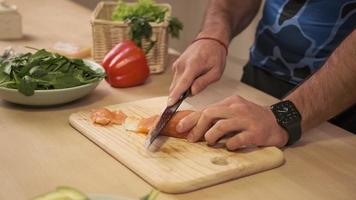 Hands cooks close-up. The chef cuts with a knife a red fish, smoked salmon on a wooden cutting board. photo
