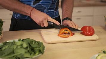 Cocinero corta pimiento dulce con un cuchillo de cocina grande sobre una tabla de cortar de madera para cocina. la parte superior del tallo está cortada en rodajas. Vista cercana de rebanar pimiento. concepto saludable. foto