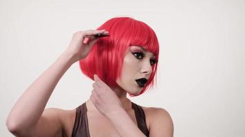Young woman styling her short shiny dyed hair with comb, care concept, combing red hair wig, 4k photo
