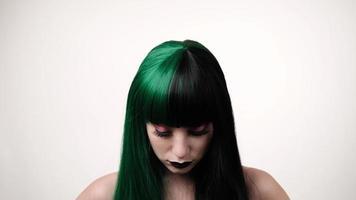 Retrato de mujer caucásica con estilo alegre en peluca negro-verde sobre fondo lifht. extraordinario encanto femenino. concepto de mirada de muñeca. foto