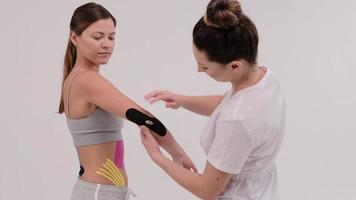 A female physiotherapist is measuring a piece of kinesiotape to be applied on a shoulder joint. He folds a hand in the elbow to check photo