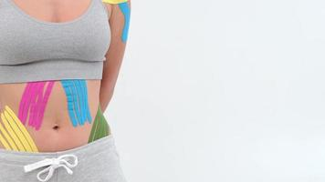 Kinesiology tape on girl belly. body with kinesio tape on the abdomen of young girl. Sport tratment rehabilitation photo