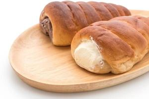 Bread roll with cream on wood plate photo