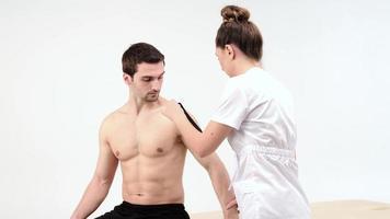 tratamiento de hombros con kinesio tape. Fisioterapeuta aplicando cinta terapéutica elástica a la lesión del hombro del paciente foto