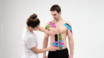 Female therapist applying kinesiology tape on a man's abdomen on the light background. Woman prepares male patient to glue kinesio adhesive tape on his belly photo