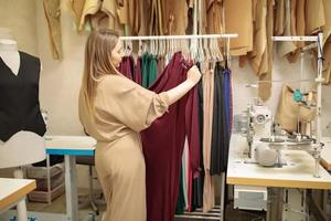 Successful young Caucasian female fashion designer or stylist manage new clothes collection on rack in studio showroom, millennial woman tailor dressmaker prepare wardrobe clothing photo