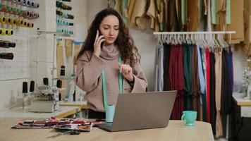 Successful tailor entrepreneur is talking on mobile phone and using laptop. Woman is busy ordering fabric from textile supplier. Clothing design start-up concept. photo