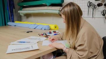 Close up of female designer using pencil and sheet of paper for fashion sketches. Tailor woman creating design of new clothing collection at studio photo