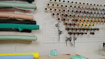 Workshop of tailor studio, tailoring wear to order. interior of small fashion studio. View of rolls of fabric, spools of thread and patterns photo