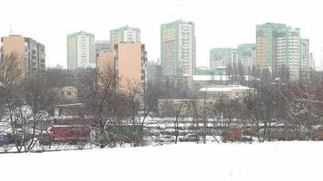 It is snowing. Snow-covered multi-storey tipical building. Winter, empty city. photo