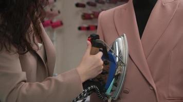 Siview tilt down medium shot of female tailor steaming jacket on a mannequin dummy in workshop photo