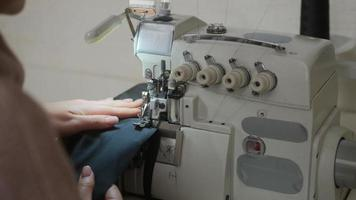 Stitching on sewing machine. Tailor sews on sewing machine. Close-up of woman's hand and sewing process. photo