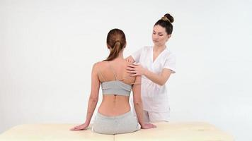 Physical Therapist Massaging Shoulder of a Female Patient. Over shoulder view of masseur performing deep tissue massage. 4k stock footage. close up video. photo