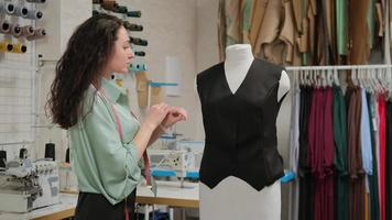 Dressmaker pins up a jacket in the initial stage of tailoring using sewing pins in a sewing workshop studio photo