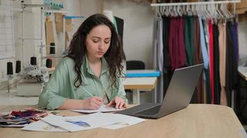Focused young female tailor writing notes in paper, using laptop. Concentrated fashion designer entrepreneur in working on laptop, managing deals online in studio photo