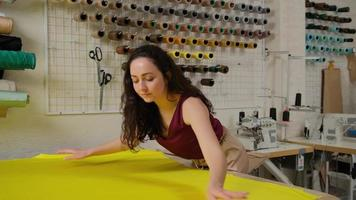 female tailor straightens yellow fabric for work on the table in the studio. photo