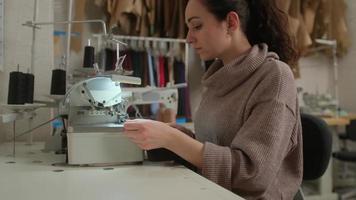 costurera trabaja en la máquina de coser. sastre se sienta a la mesa y garabatea en la máquina de coser. foto