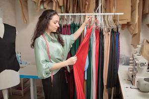 Female fashion designer working on new womenswear collection for clients in cozy workshop studio, dressmaker, tailor or needlewoman standing near clothing rack with fashionable stylish clothes photo