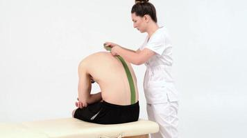 Physiotherapist sticks kinesio tapes to the back of patient, kinesiology taping, kinesiological therapy, athlete are recovering after injury of loins, 4k photo