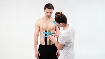 Female therapist applying kinesiology tape on a man's abdomen on the white background. Woman prepares male patient to glue kinesio adhesive tape photo