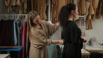 Femail seamstress taking measurements of female client using tape in atelier. Two women in tailoring studio working together. Designer and model prepairing to fashion show measuring size for dress. photo